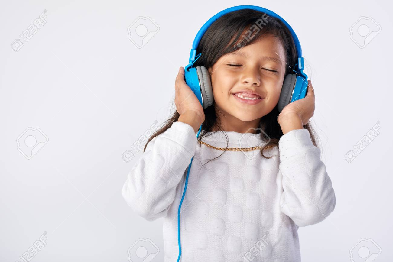 young girl playing her favorite song on headphones isolated in studio - 63979361