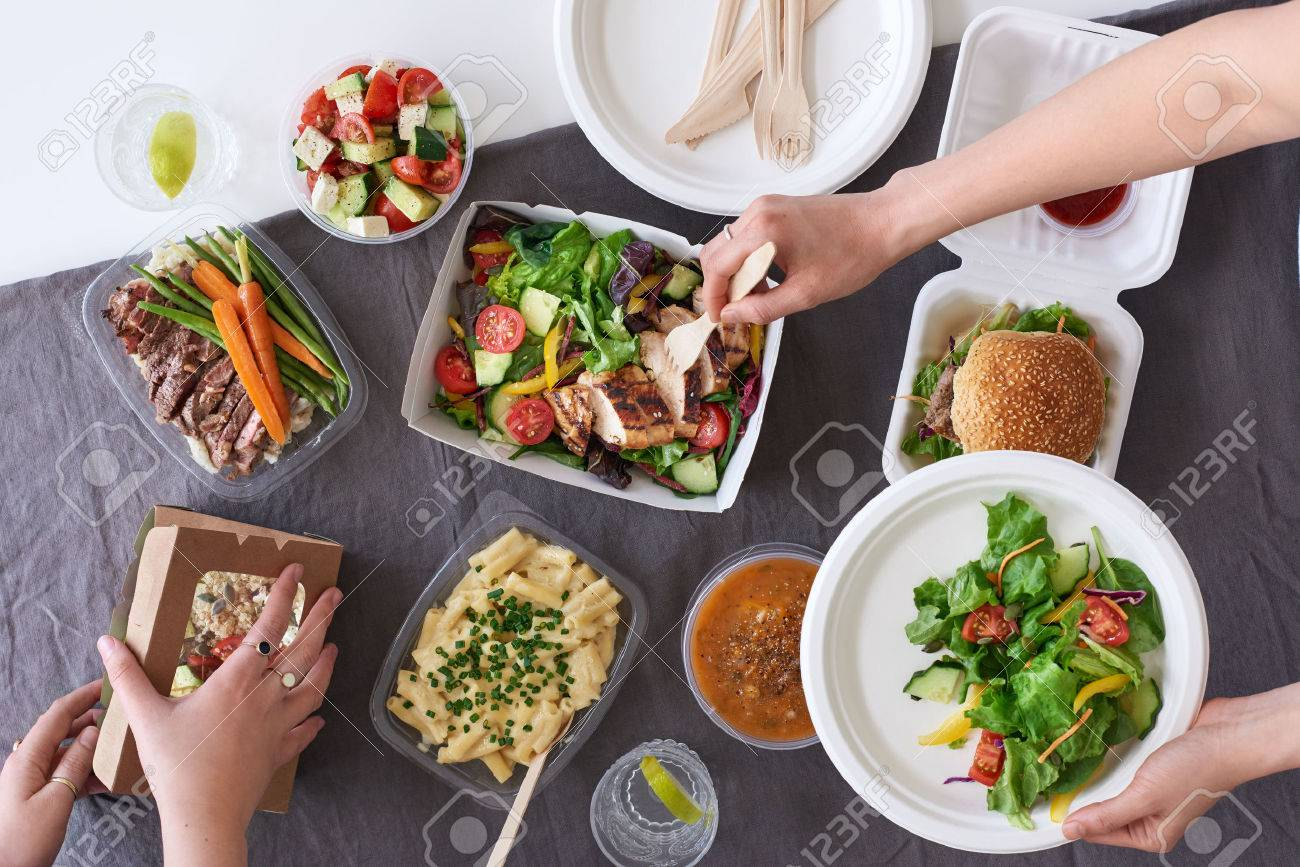 Convenient takeaway takeout food for party, overhead spread of assorted food with hands serving up - 68221382