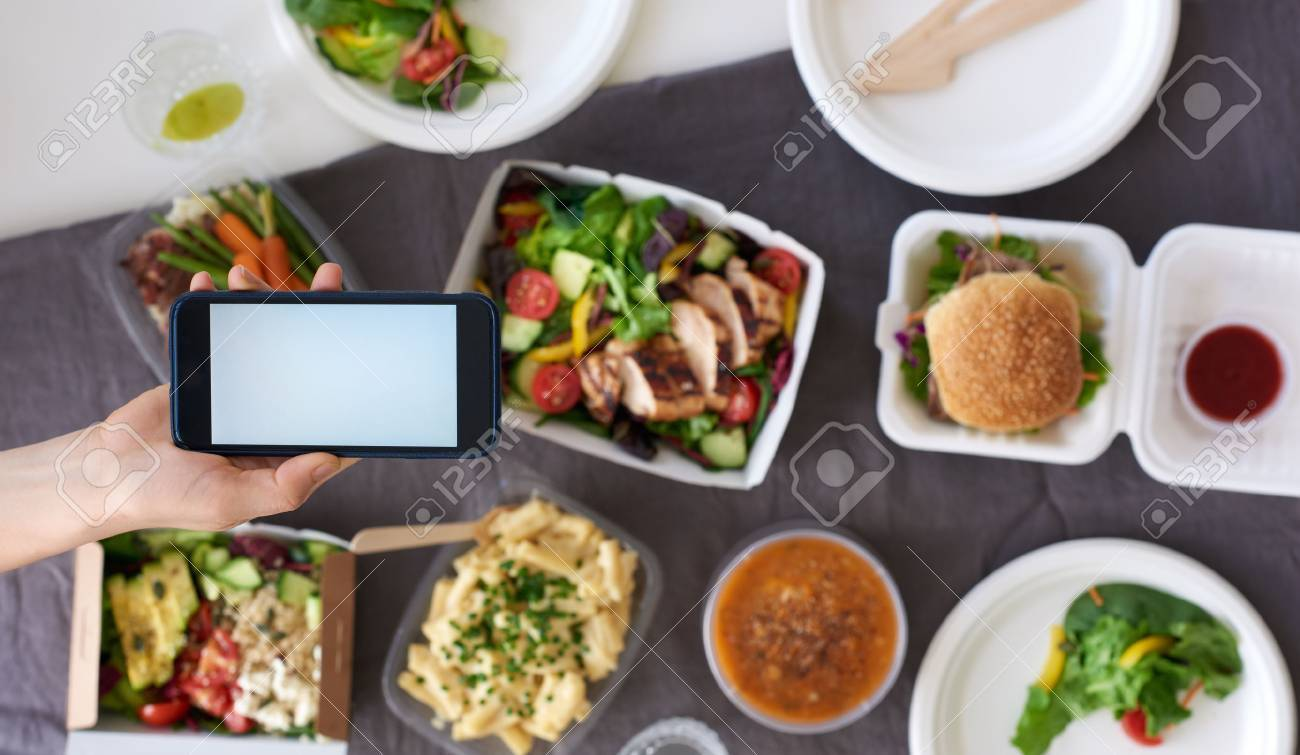 Hands holding smartphone mobile cellphone over different types of gourmet takeout, food delivery order app application concept - 68221380