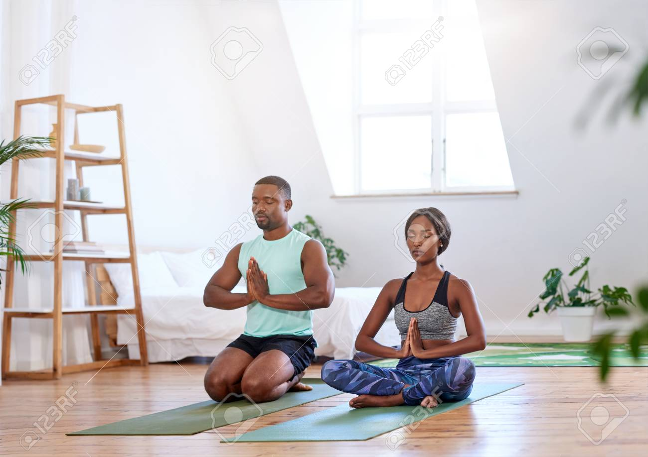 Calm relaxed couple meditating at home doing yoga relaxation - 83861819