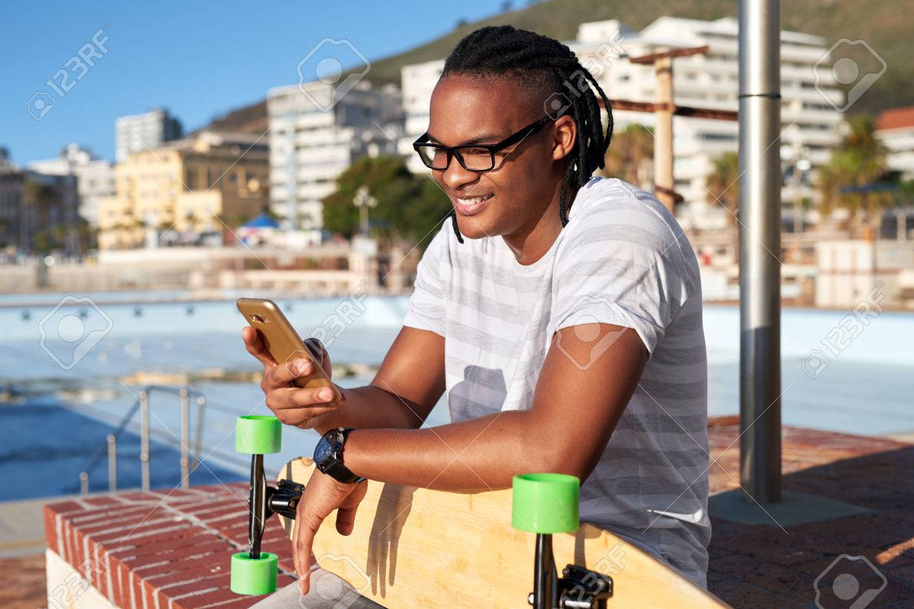 Man with longboard smiling and texting on mobile cell phone, sunny summer day - 84882338