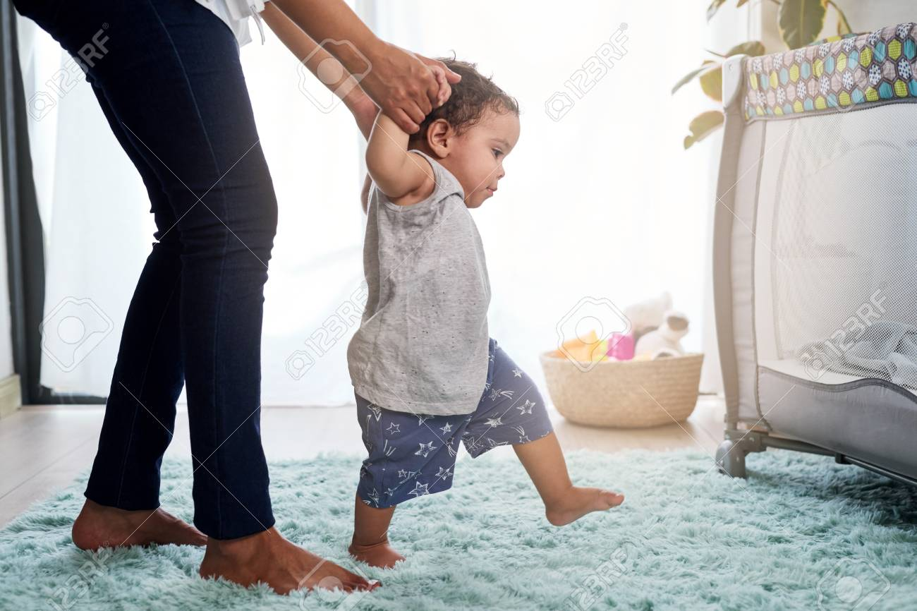 Baby's first steps holding mother's hands, cute unstable walking in home nursery with cot - 118728302