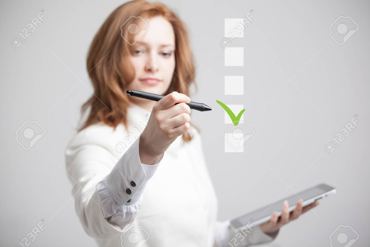 Young business woman checking on checklist box. Gray background. Concept on the topic of elections - 61971319