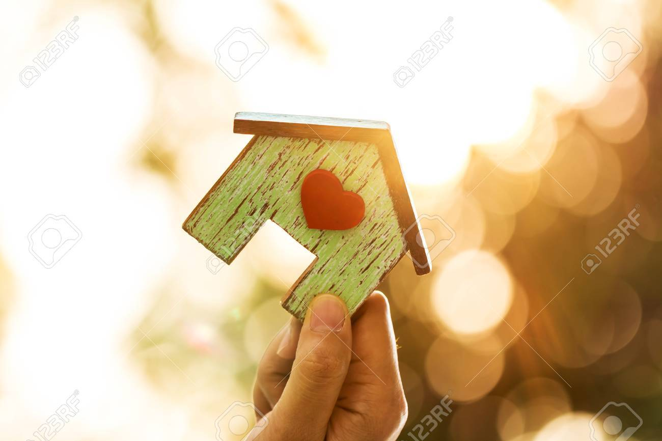 Women hand holding a home model with red heart in the sunlight in the public park, Loans for real estate or save money for buy a new house to family in the future concept. - 87155831