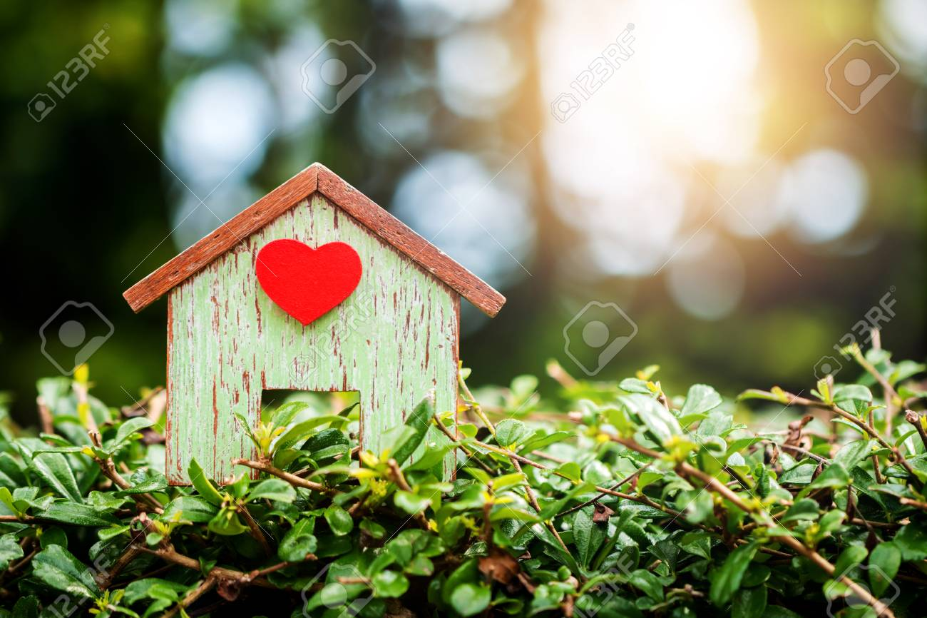 Home wooden stick a red heart put on the grass floor in the public park, Loans for real estate or save money to buy a new house for family in the future concept. - 91273105