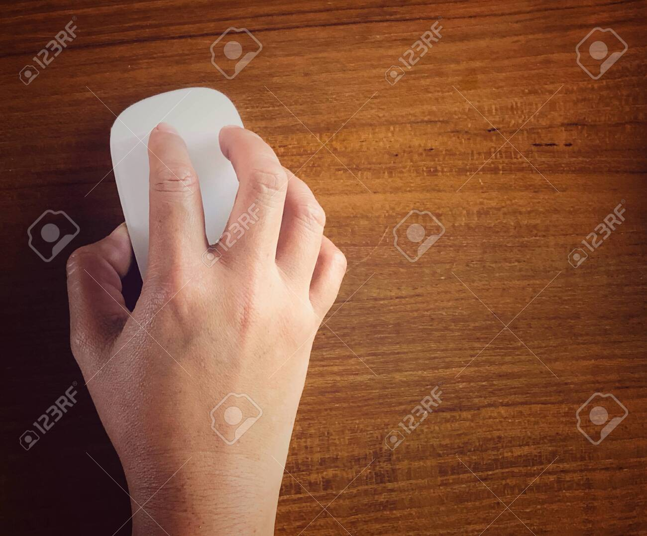 Top view of woman using computer hand holding a mouse on wooden table workong in office .Space for text ,copy space - 136817557