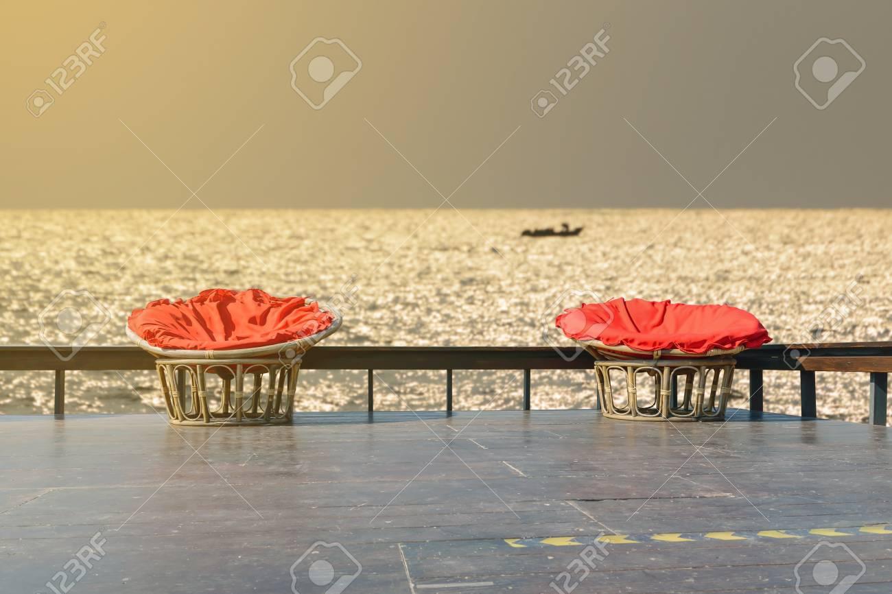 Sillas Hechas De Ratán Y Manteles De Lino En Rojo En Terraza De Madera Con El Telón De Fondo Del Arroyo
