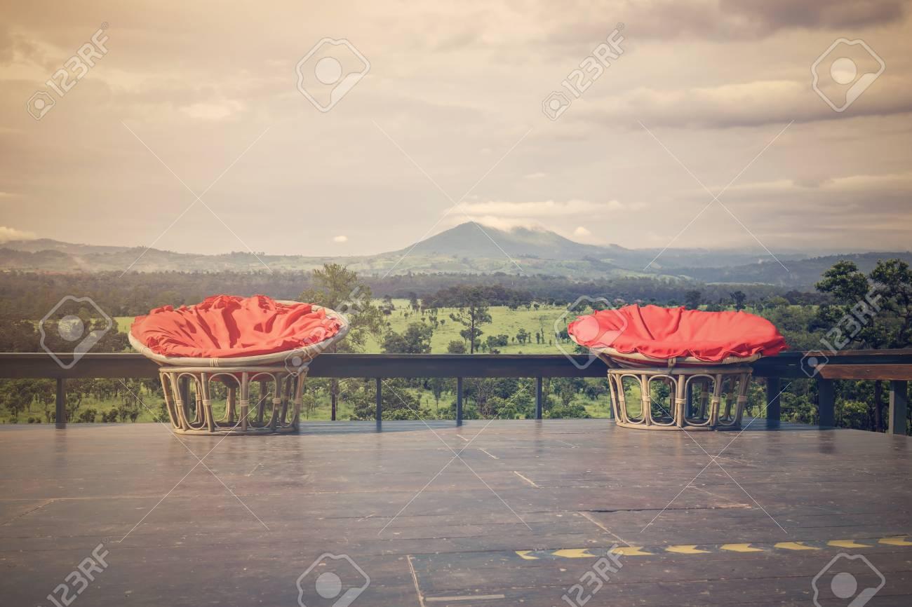 Sillas Hechas De Telas De Ratán Y Tapicería En Rojo En La Terraza De Madera Con El Telón De Fondo Del Bosque