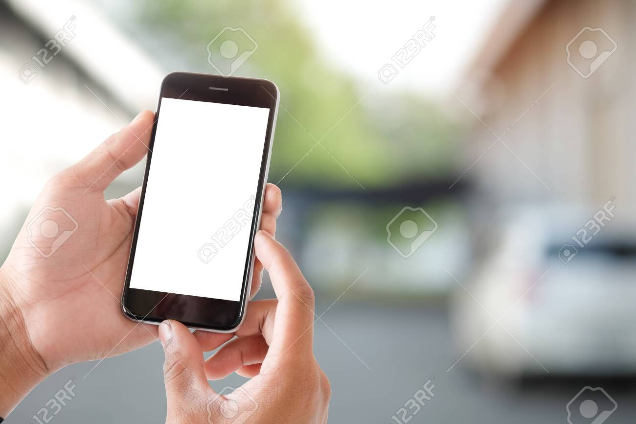 Cropped shot view of man hands holding smart phone with blank copy space screen for your text message or information content, female reading text message on cell telephone during in urban setting. - 146880008