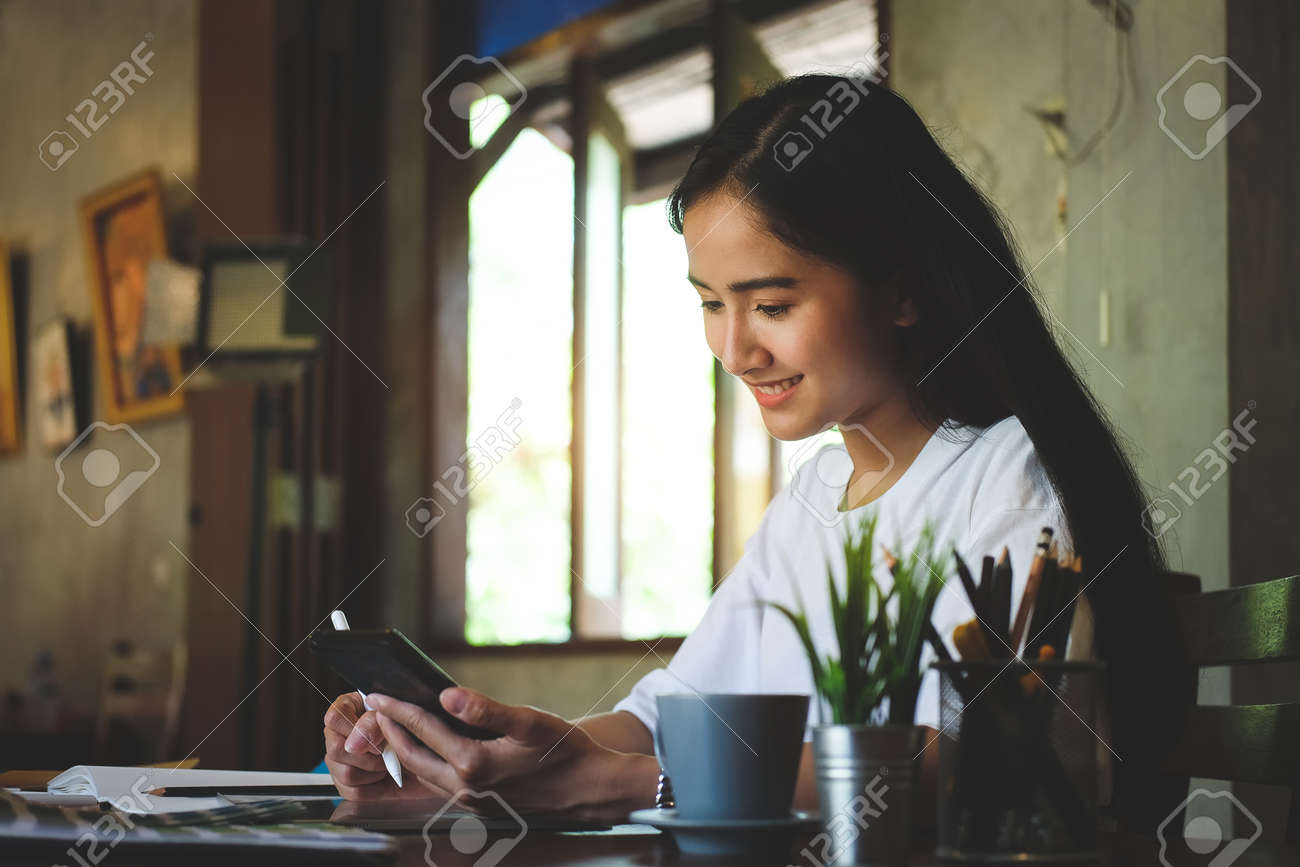 Portrait of happy young woman working on tablet pc while sitting at her working place in office. - 165898407