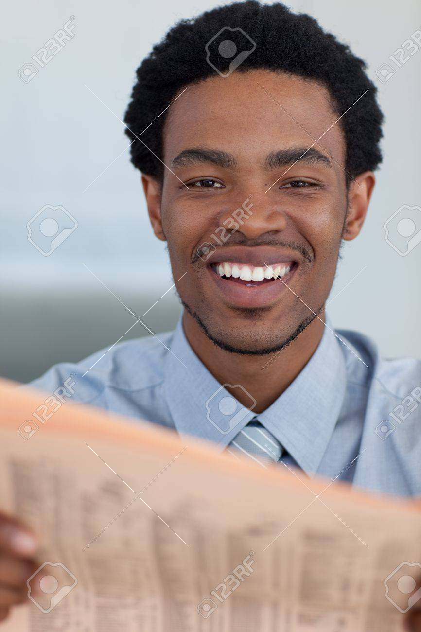Attractive Afro-American businessman reading a newspaper Stock Photo - 10074629