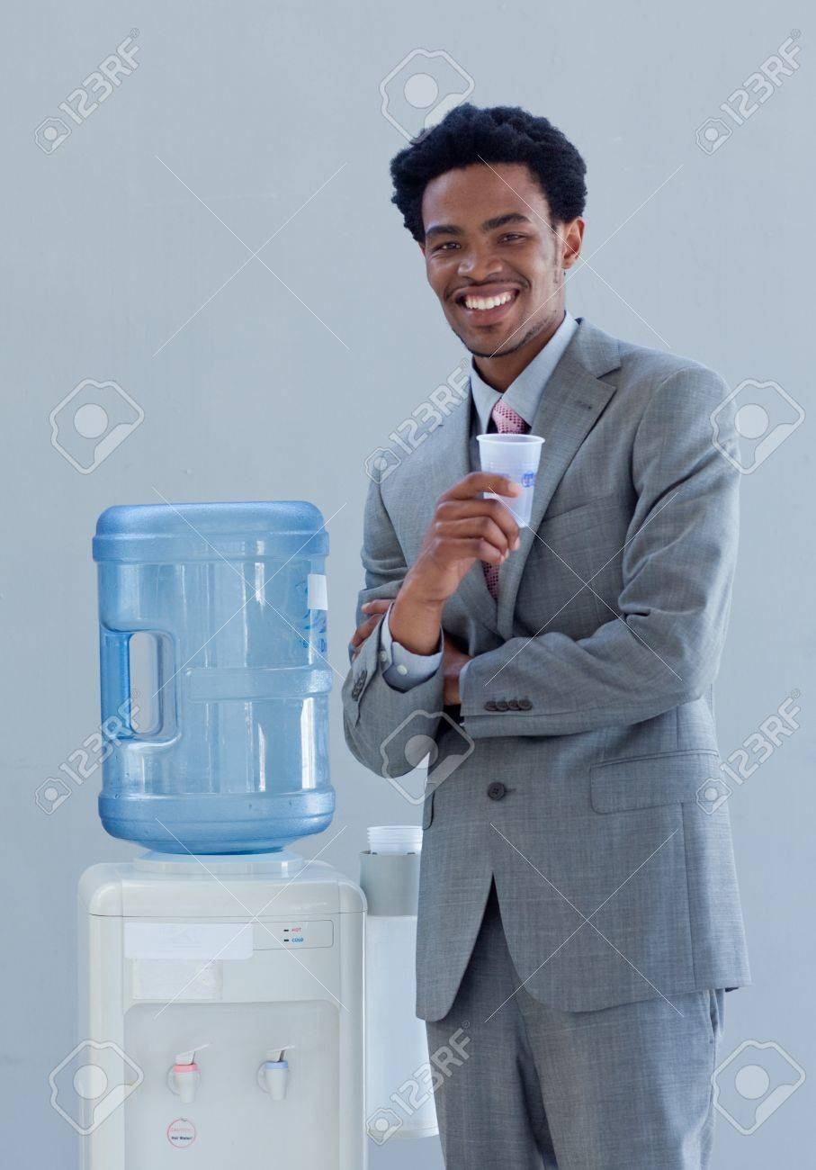 Businessman drinking from a water cooler in office Stock Photo - 10072638