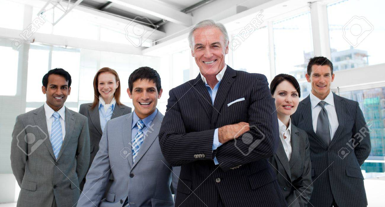 Senior manager with folded arms accompanied by his team Stock Photo - 10092878