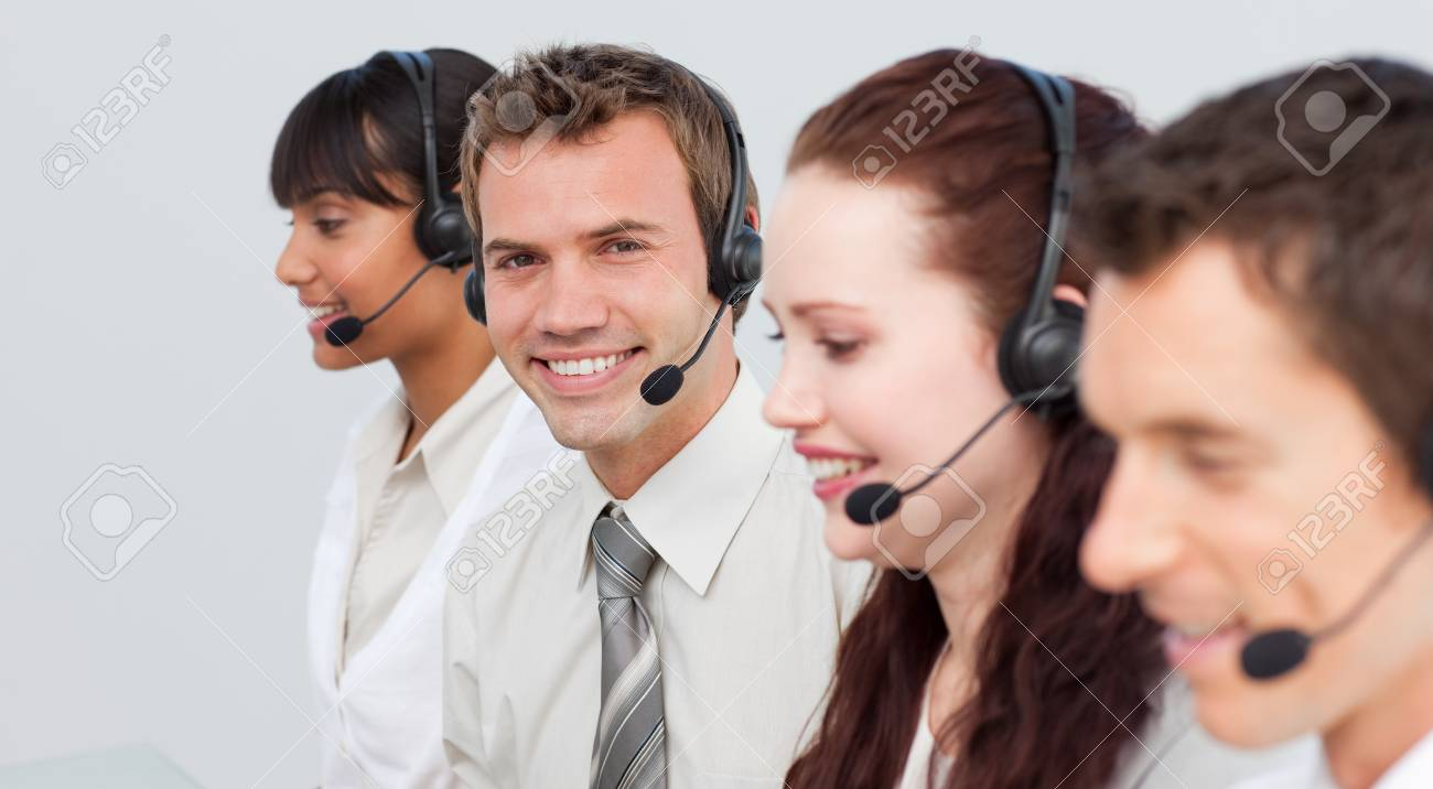 Smiling man working in a call center with his colleagues Stock Photo - 10078648