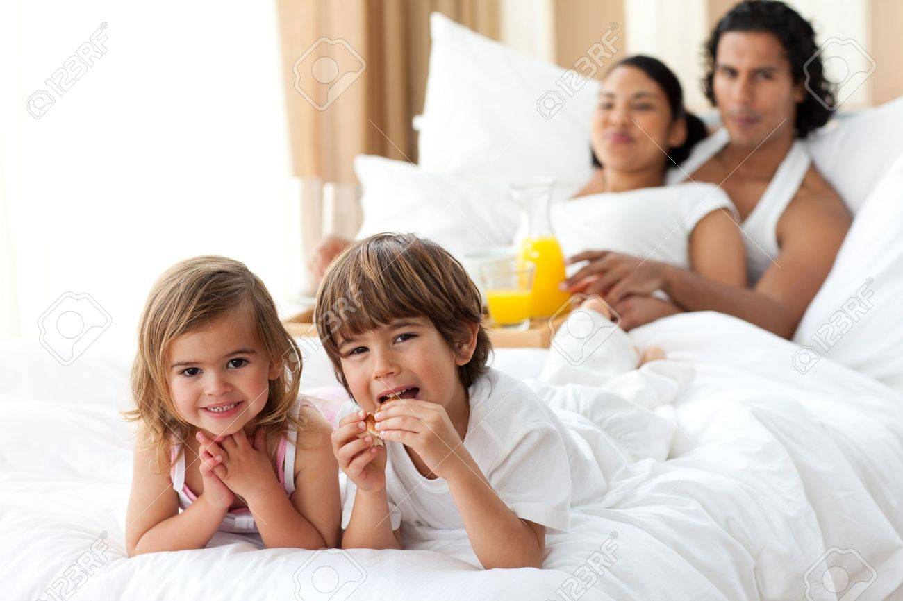 Happy siblings having breakfast with their parents Stock Photo - 10096843