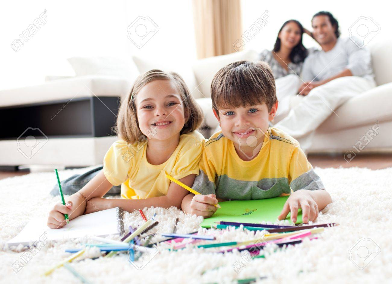 Portrait of cute siblings drawing lying on the floor Stock Photo - 10095980