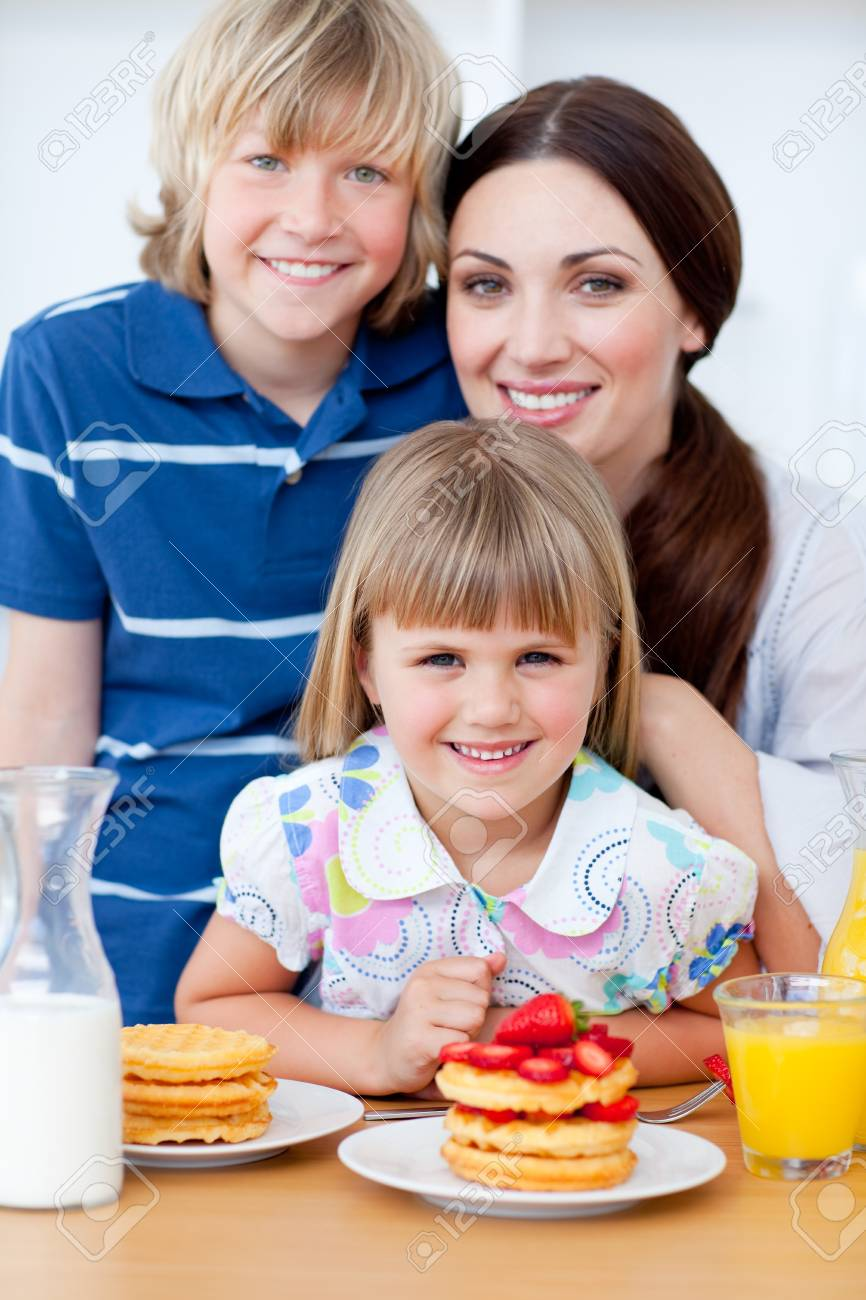 Portrait of a mother and her children having breakfast Stock Photo - 10097379