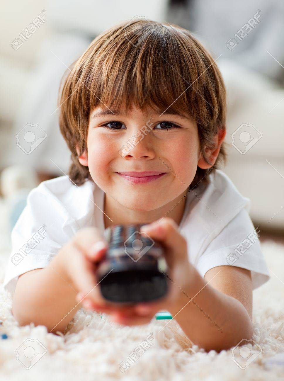 Smiling little boy watching TV lying on the floor - 10107114