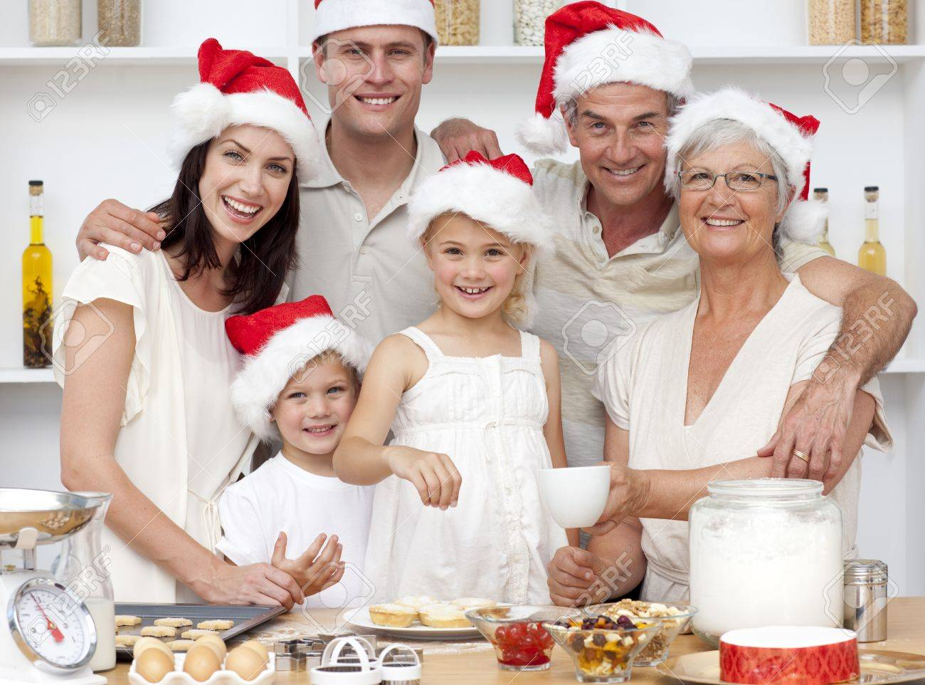 Children baking Christmas cakes in the kitchen with their family Stock Photo - 10107405