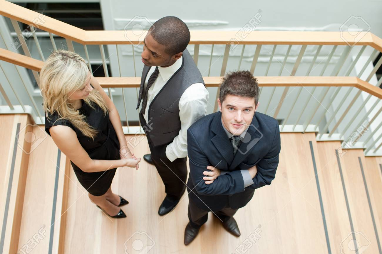 Businessman and businesswoman shaking hands and a man with folded arms Stock Photo - 10111195