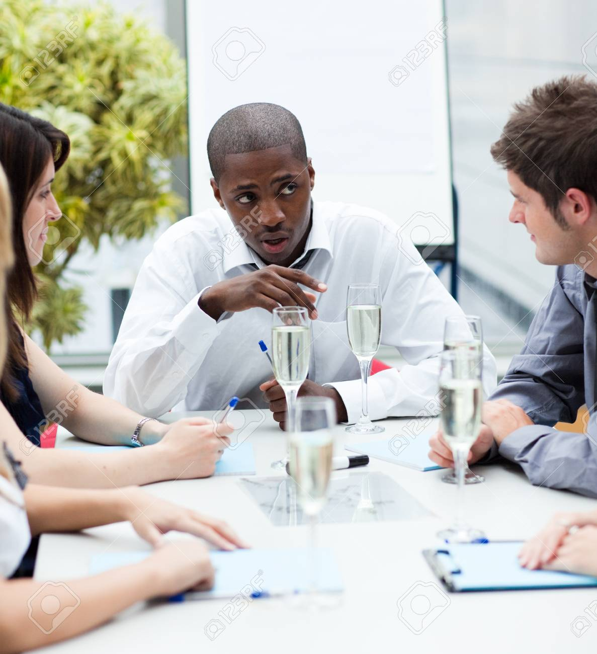Ethnic manager speaking in a meeting with champagne Stock Photo - 10111535