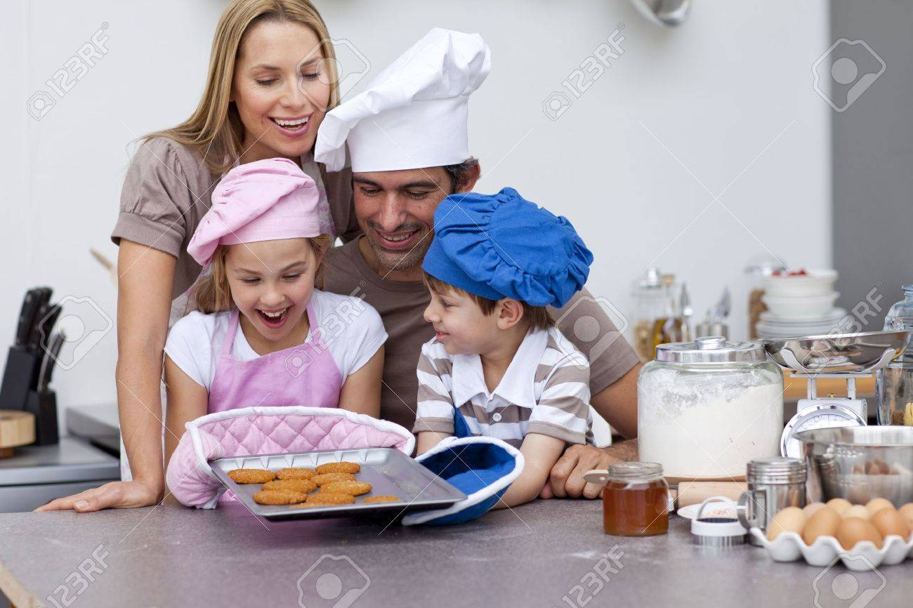 Happy family in kitchen - Happy Family Baking Cookies In The Kitchen Stock Photo 10129081