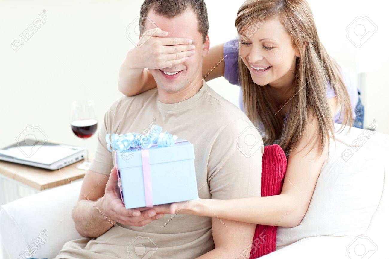 Smiling woman giving a present to her boyfriend Stock Photo - 10129342