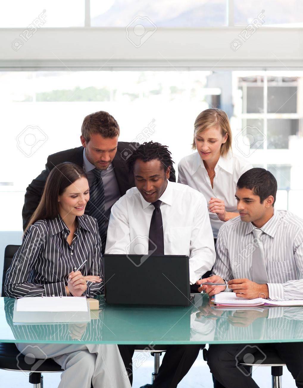 Business people using a laptop together Stock Photo - 10114796
