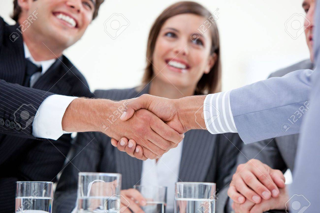 Smiling business people closing a deal Stock Photo - 10131872