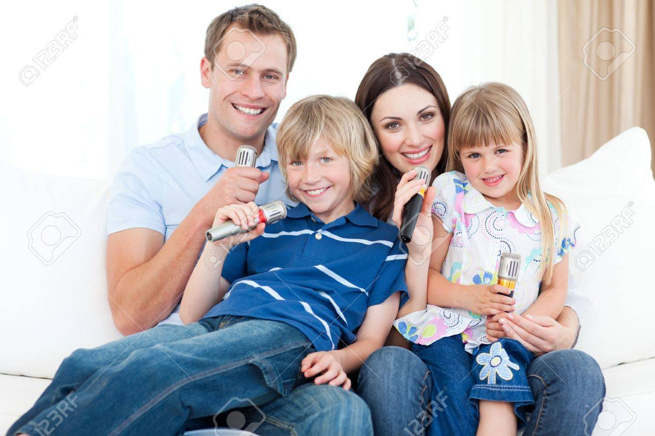 Smiling young family singing a karaoke together Stock Photo - 10134338