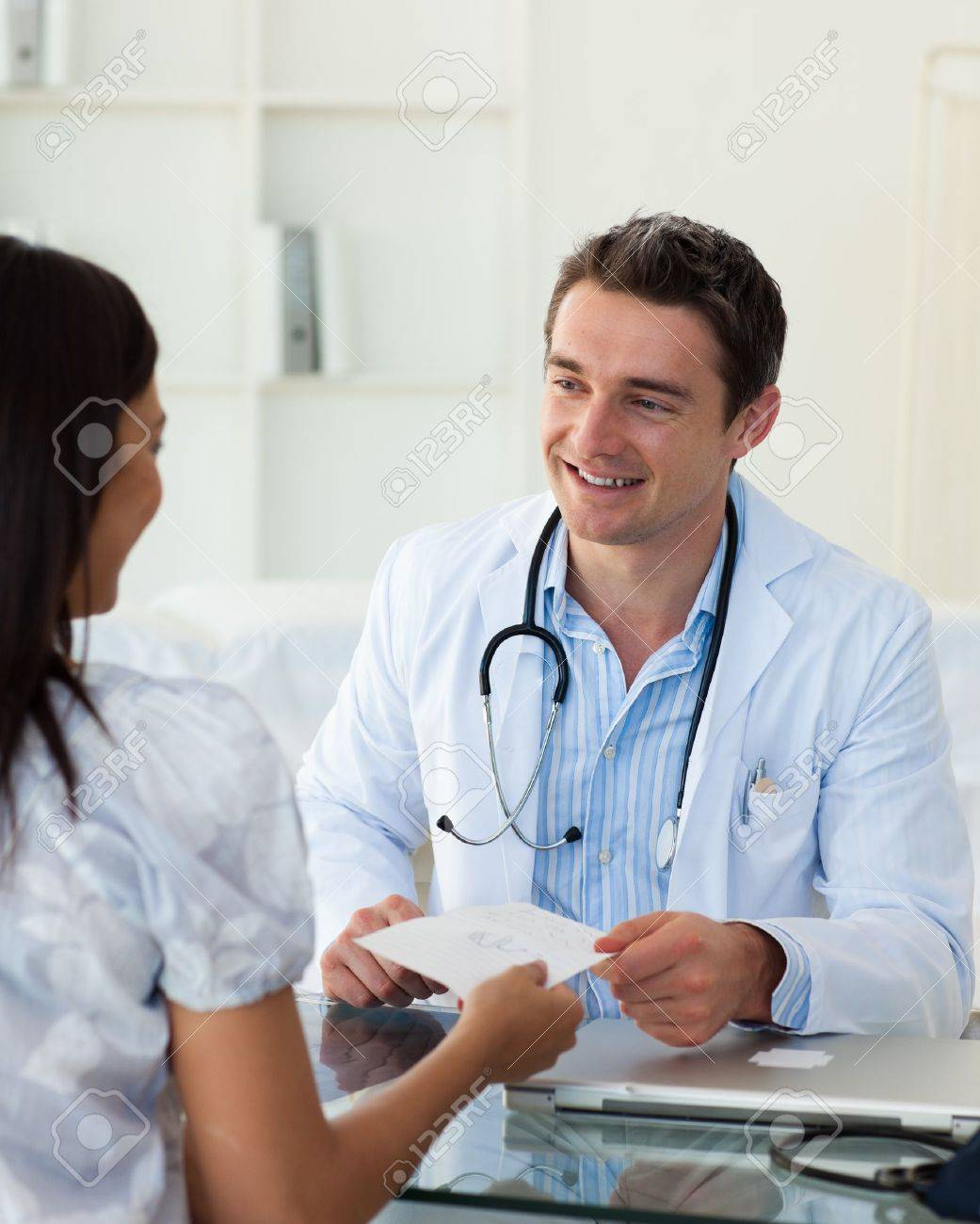 Smiling doctor giving a prescription to his female patient Stock Photo - 10131031