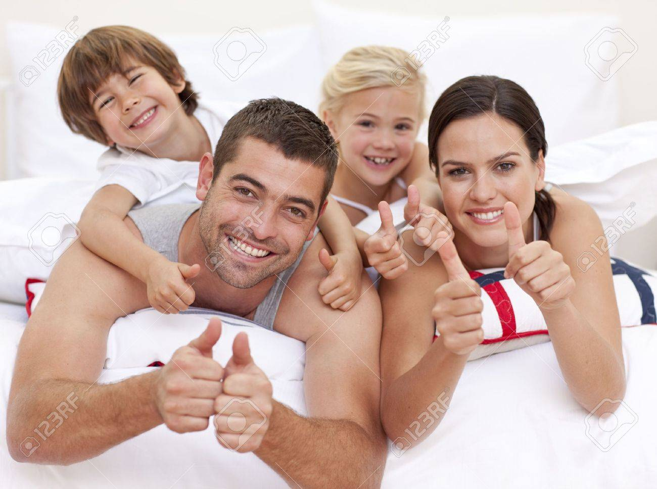 Family playing in bed with thumbs up Stock Photo - 10131632