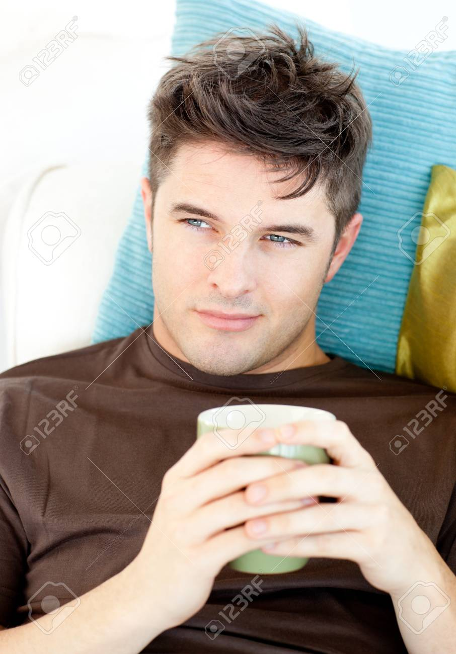 Charismatic young man holding a cup lying on the sofa Stock Photo - 10133691