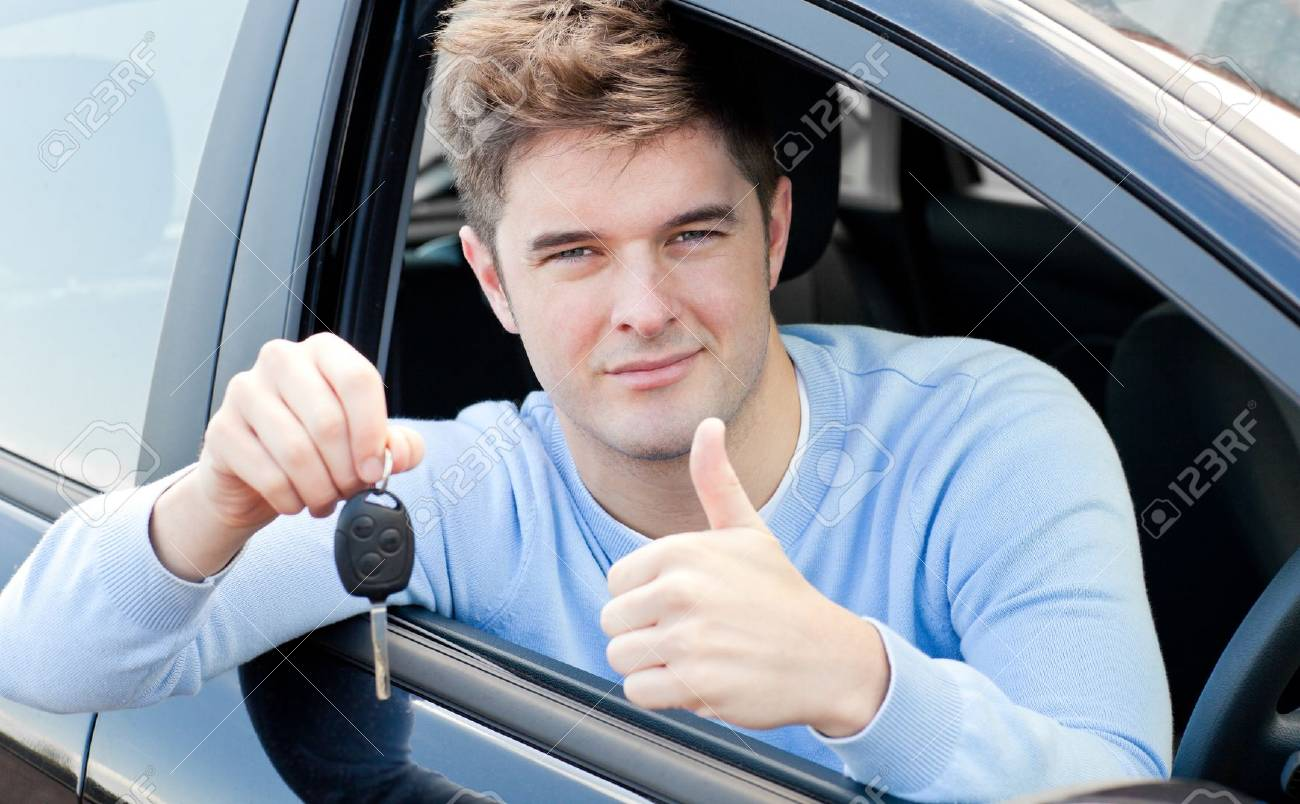 Positive young man holding a key sitting in a car Stock Photo - 10134398