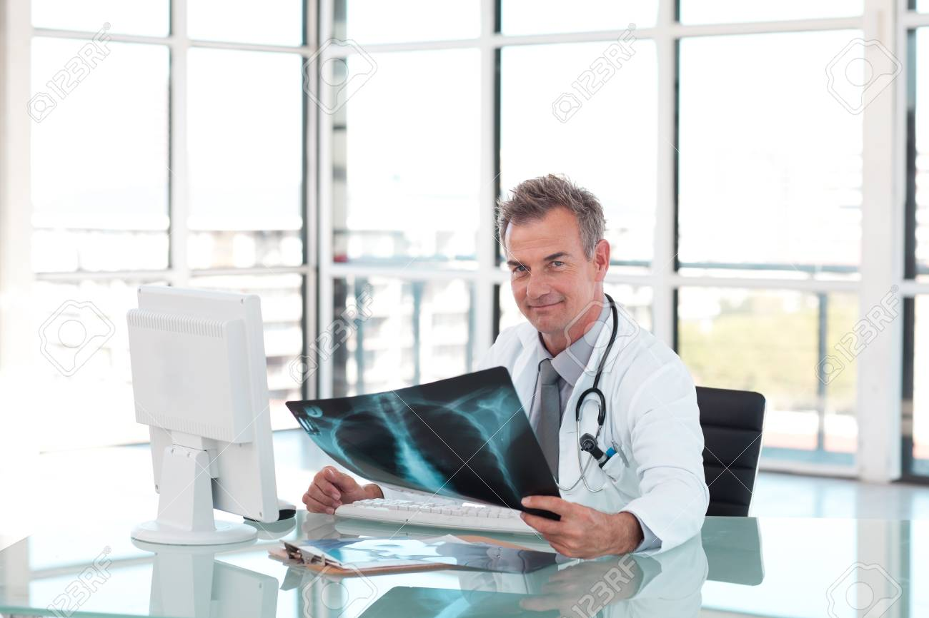 mature doctor looking at an x-ray stock photo, picture and royalty