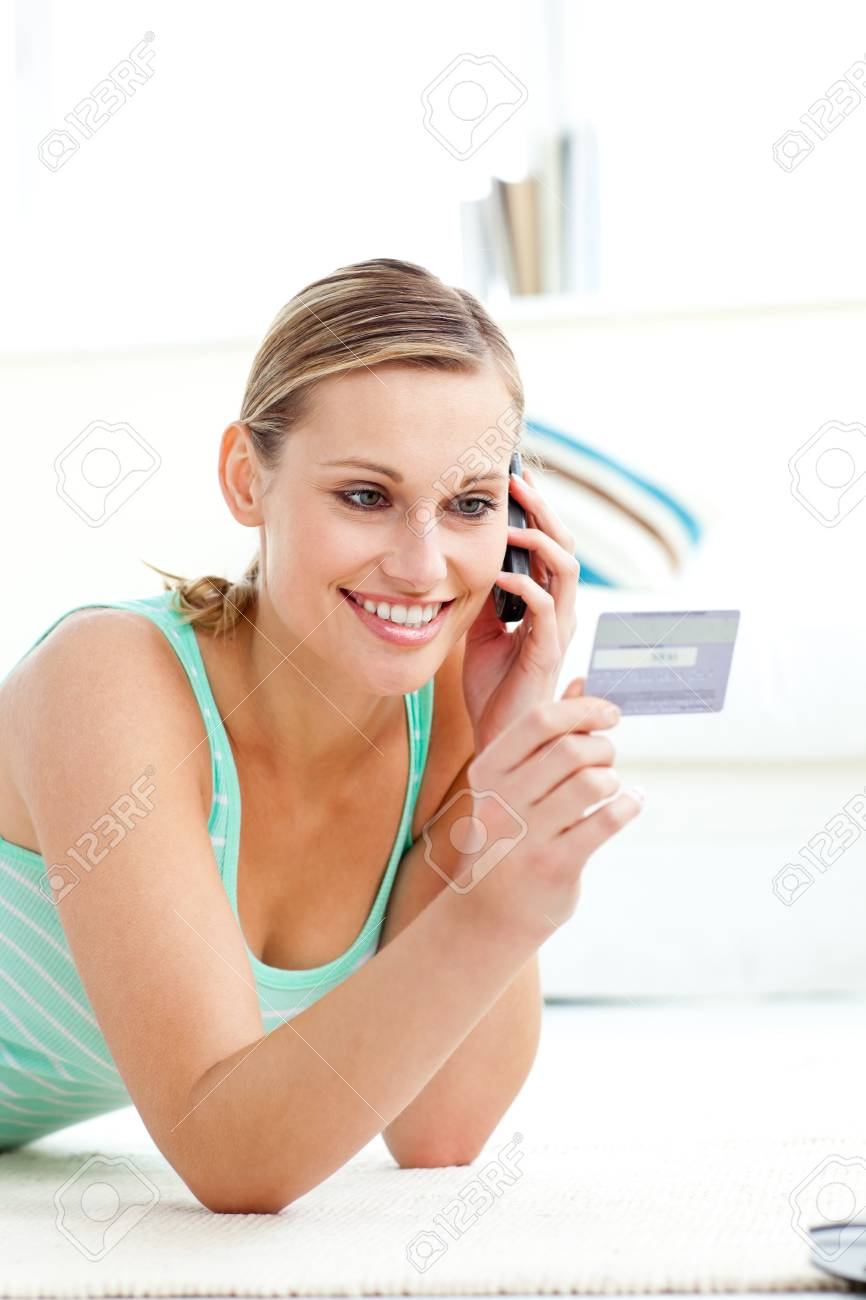 Charming young woman talking on phone holding a card Stock Photo - 10161768