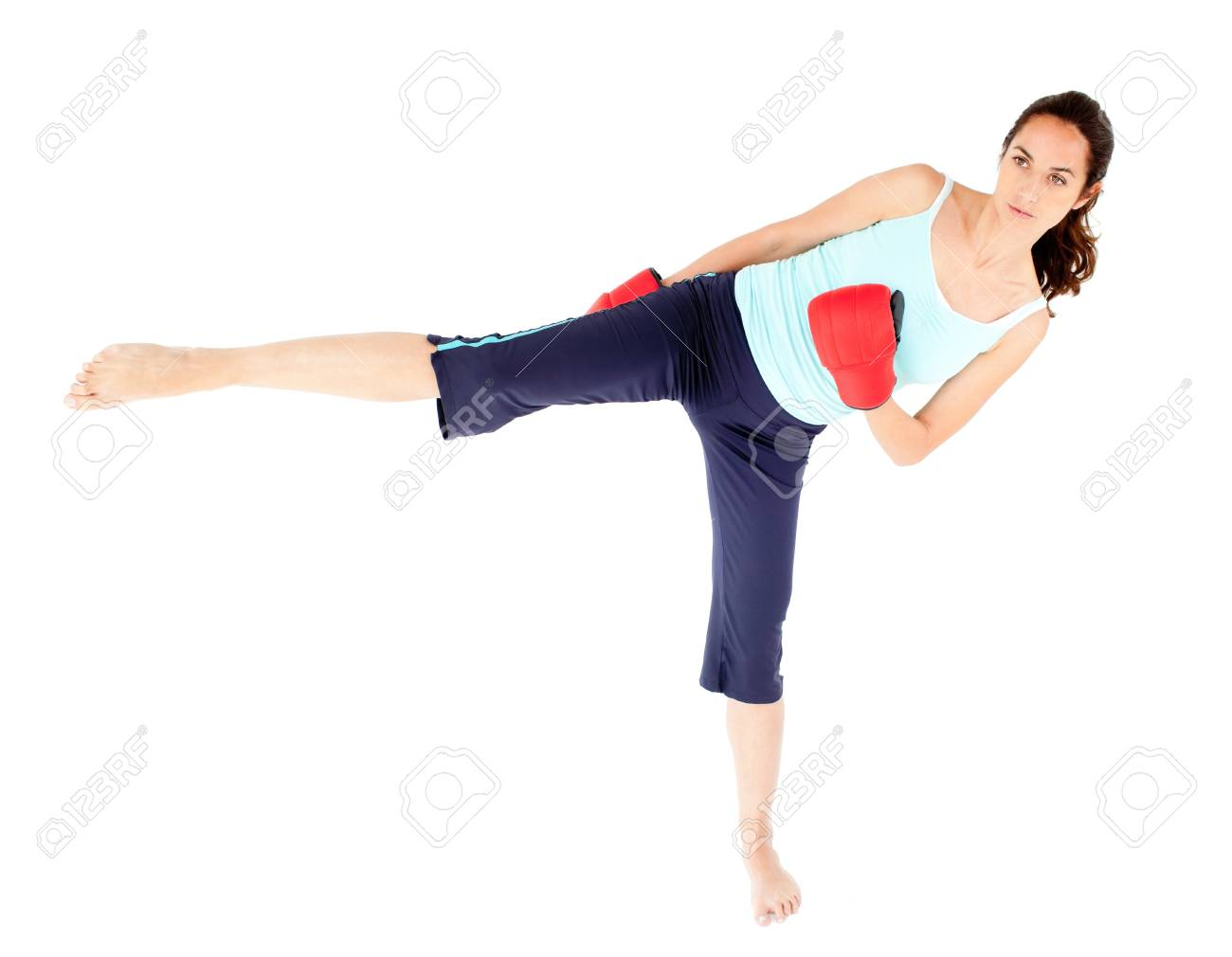 Concentrated woman wearing boxing gloves giving a kick Stock Photo - 10134987