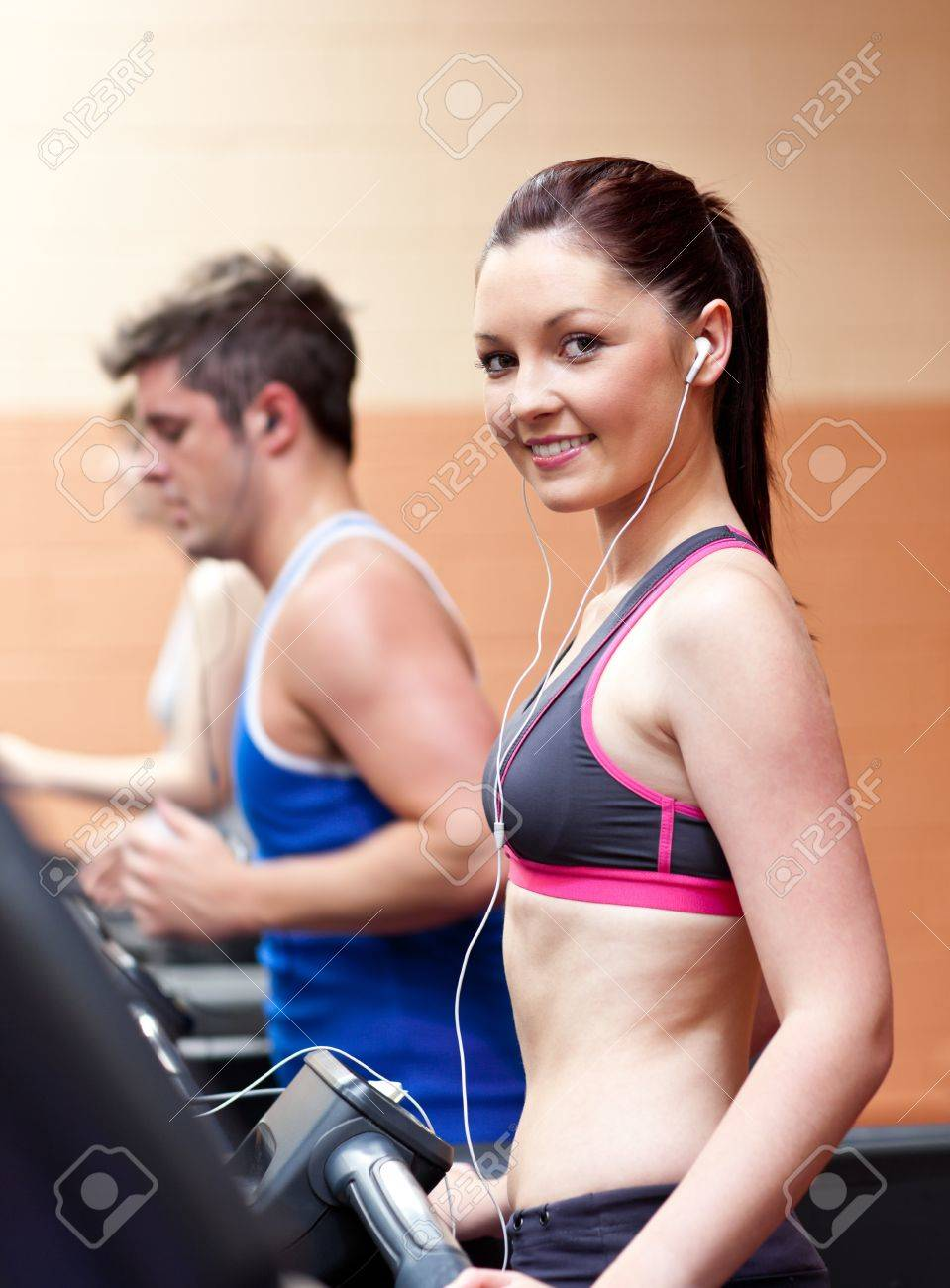 Cute athletic woman standing on a running machine with earphones Stock Photo - 10164129