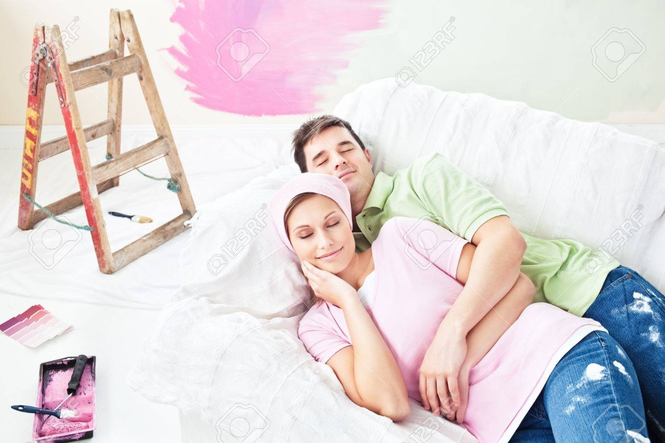 Delighted couple lying on the sofa after painting their new room Stock Photo - 10170598