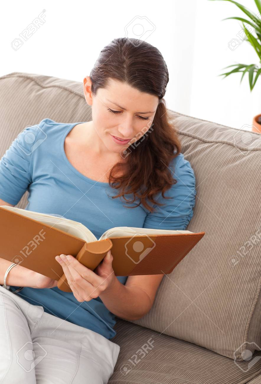 Attentive woman reading a book sitting on her sofa Stock Photo - 10175354