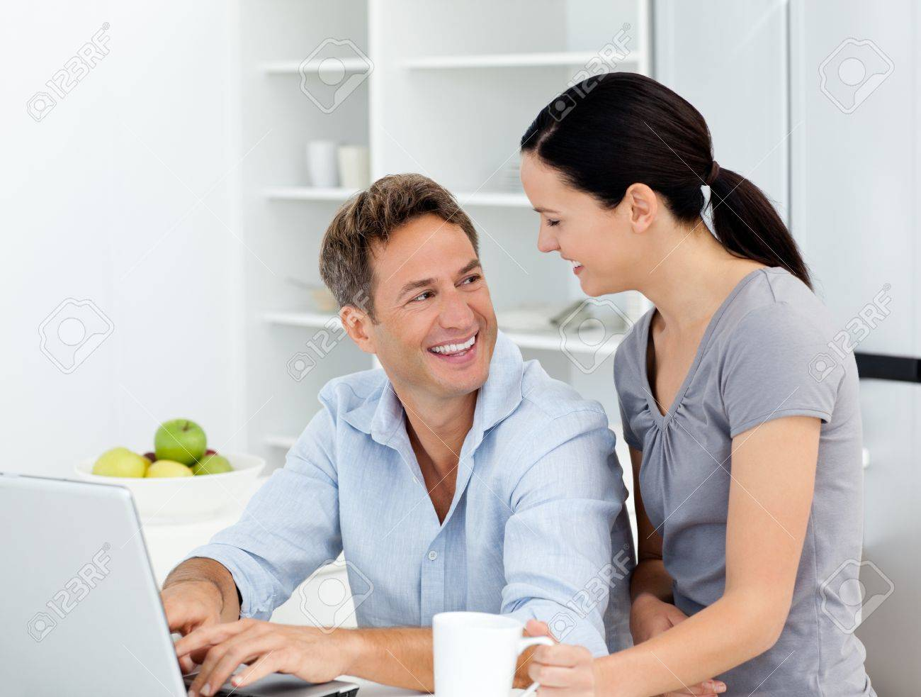 Happy couple working on their laptop in the kitchen Stock Photo - 10175491