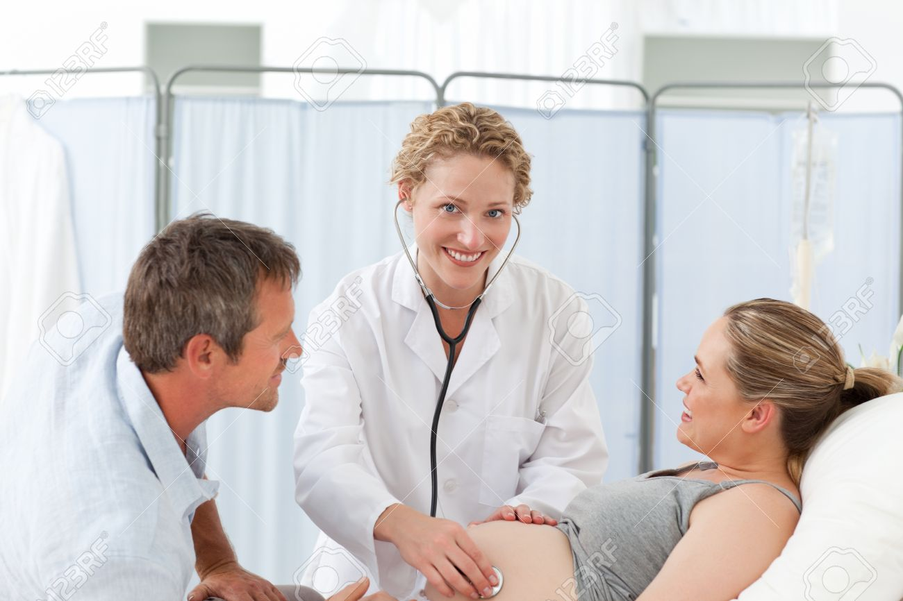 Pregnant woman with her husband and the nurse looking at the camera Stock Photo - 10173381