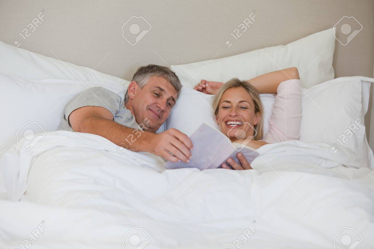 Couple reading a book in their bed Stock Photo - 10175666