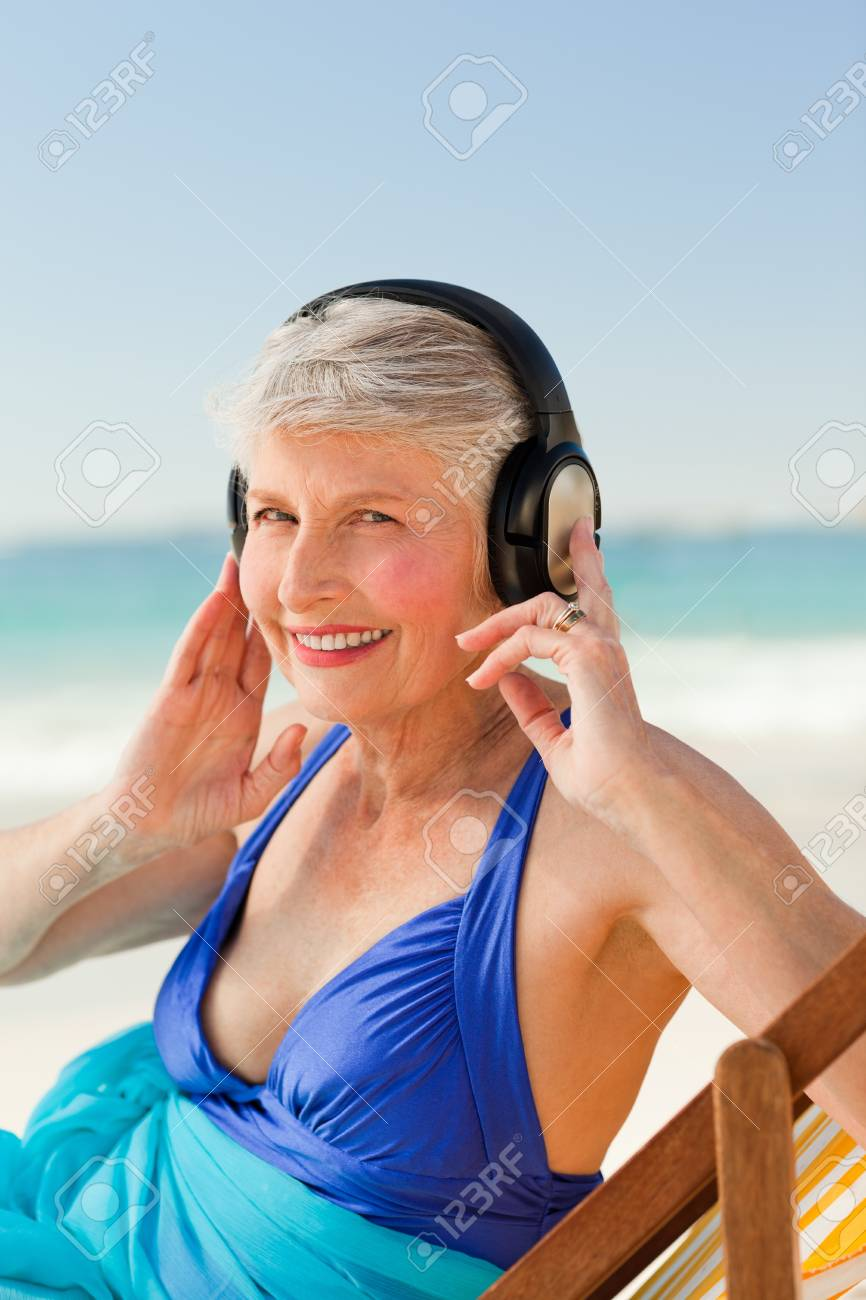 Retired woman listening to music at the beach Stock Photo - 10169822