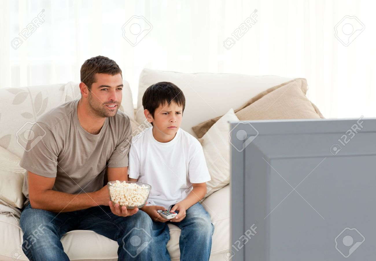 Concentrated father and son watching television while eating pop corn Stock Photo - 10196607