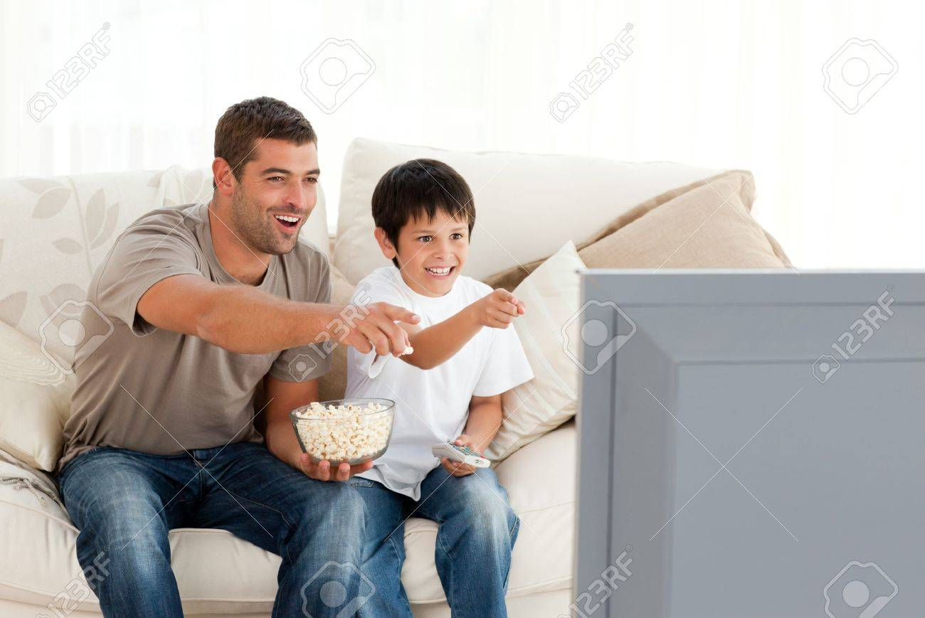 Happy father and son watching television while eating pop corn - 10196908