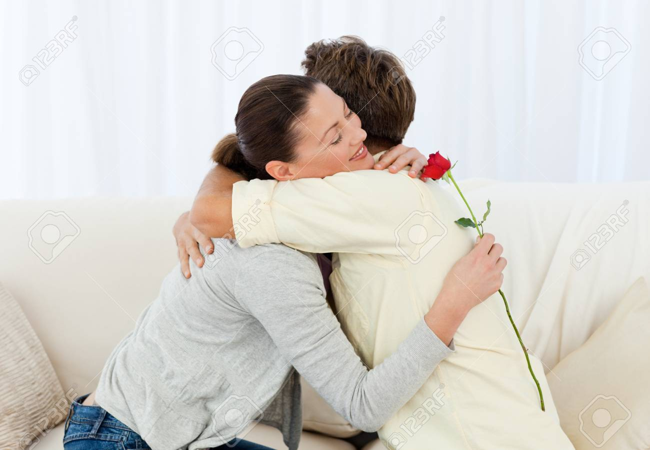Lovely woman hugging his boyfriend after receiving a flower Stock Photo - 10182558