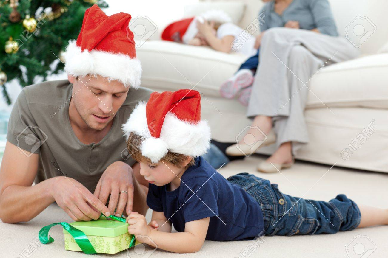 Father and son unwrapping a present lying on the floor Stock Photo - 10185103
