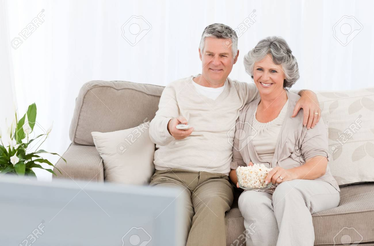 Mature couple watching tv in their living room at home Stock Photo - 10196727