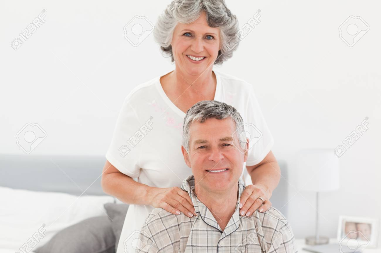 Retired woman giving a massage to her husband at home Stock Photo - 10197089